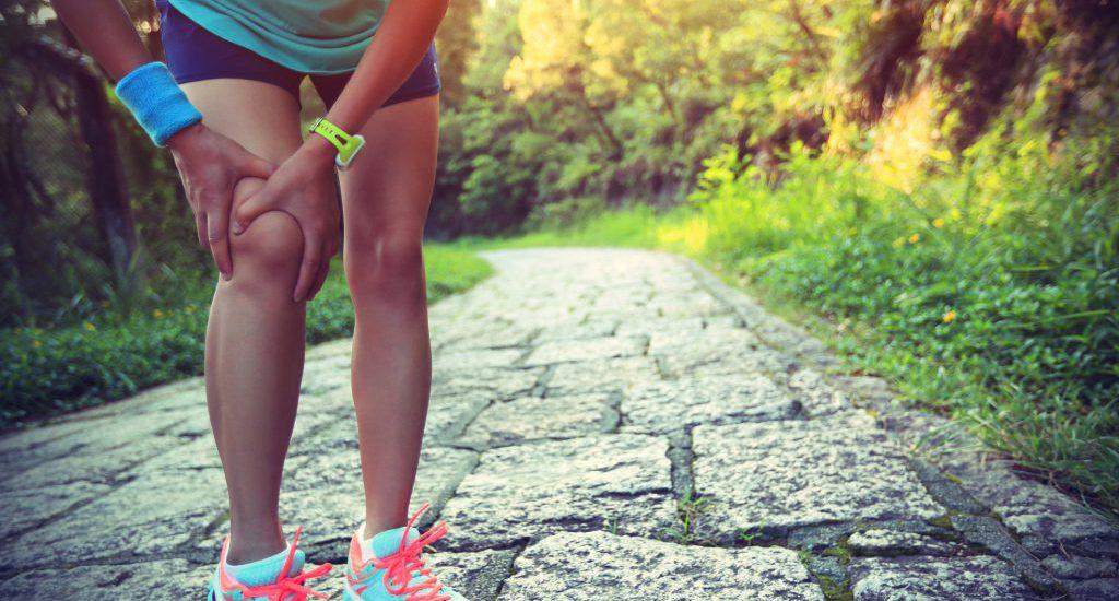 woman runner holds her injured knee
